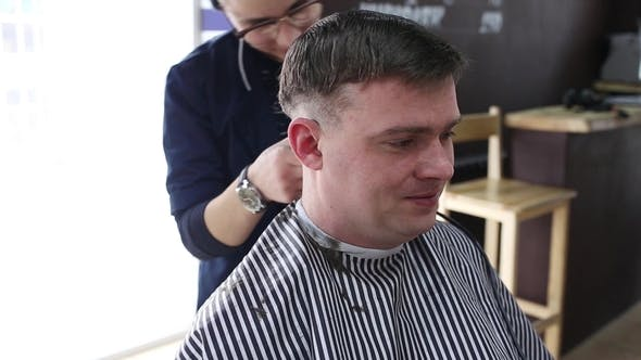 The Gay Boy Hairdresser Makes A Stylish Hairstyle For A Male Client