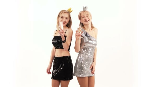 2 Beautiful Cheerful Twin Girls With Glasses Of Champagne Posing In The Studio Stock Footage