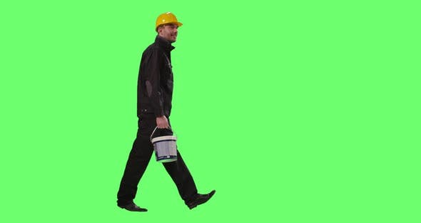 Construction Worker in a Hard Hat Carrying Paint Bucket is Walking on a  Mock-up Green Screen (Stock Footage) 1c3f3ebb9a2